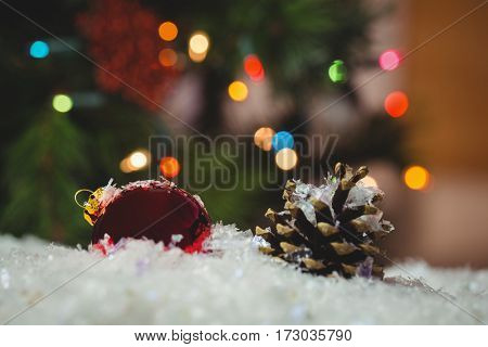 Christmas bauble and pine cone on snow on snow during christmas time