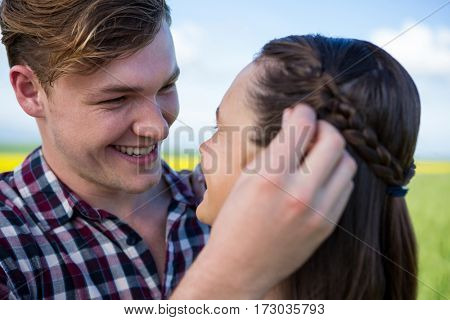 Romantic couple looking at each other in field on a sunny day