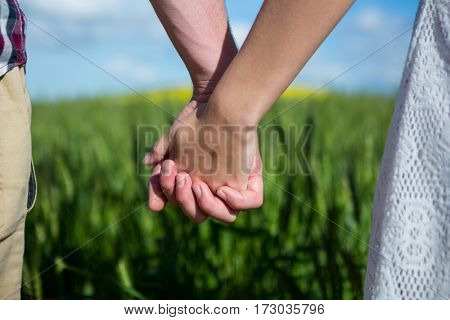 Mid section of couple holding hands in field on a sunny day