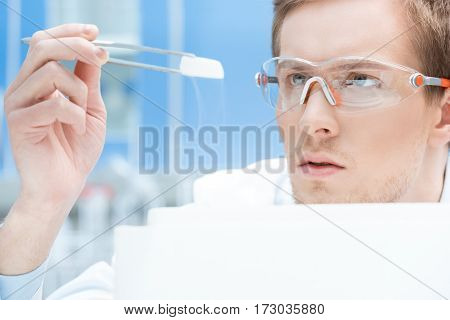 concentrated scientist in protective glasses and gloves looking at chemical sample
