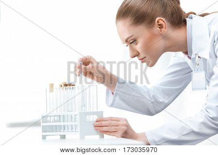 Side view of young woman scientist working with test tubes on white