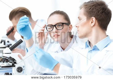 Young man chemist in protective gloves showing test tube to colleague