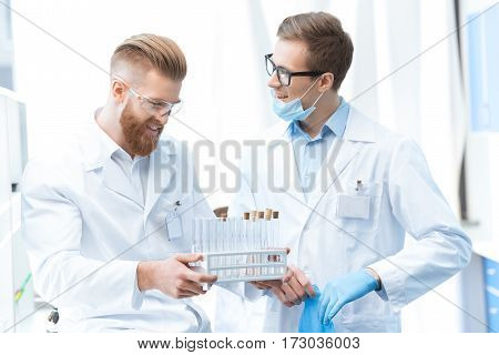 Young smiling men chemists in white coats holding test tubes in laboratory