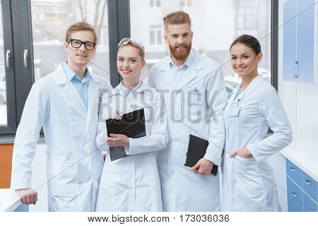 Team of young professional scientists in white coats smiling at camera in laboratory