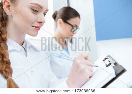 Young women scientists in white coats taking notes in laboratory