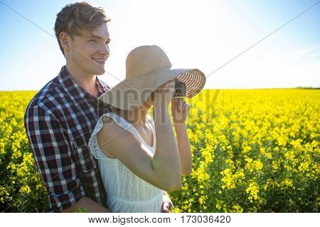 Couple taking picture from camera in mustard field on a sunny day