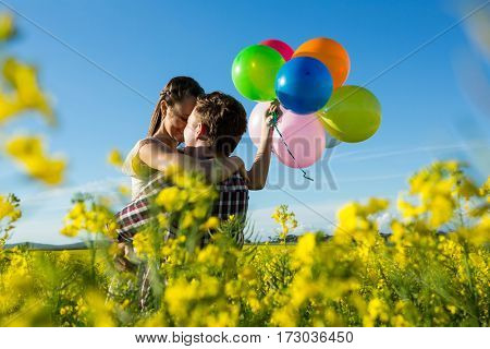 Couple holding colorful balloons and embracing each other in mustard field on a sunny day