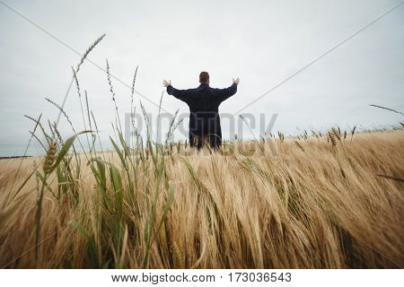 Rear view of farmer standing with arms outstretched in the field on a sunny day