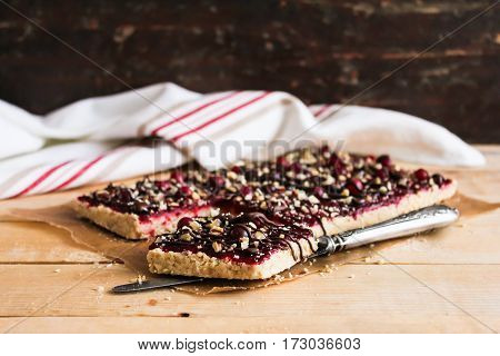 Homemade sweet pie with cranberry jam, dark chocolate and walnuts on a wooden table, selective focus