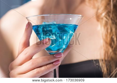 partial close up view of woman holding in hand cocktail drink