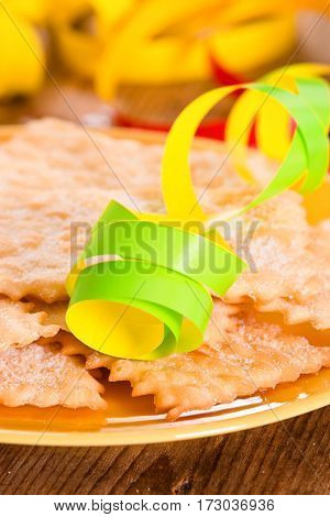 Carnival pastry with confetti on wooden table.