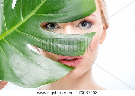 Beautiful blonde woman with stylish makeup looking through green leaf skincare concept