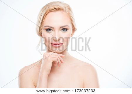 Gorgeous naked blonde woman with hand on chin smiling at camera body care concept