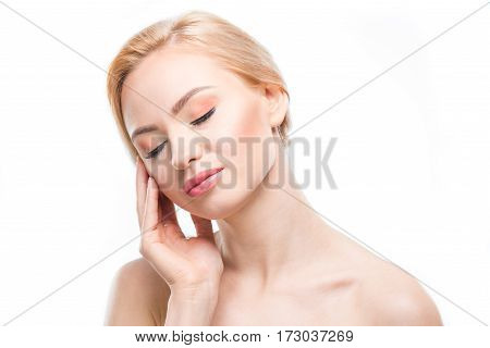 Portrait of gorgeous naked blonde woman with closed eyes posing on white body care concept