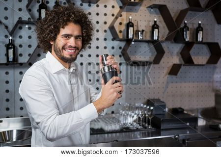 Portrait of happy waiter shaking drink in cocktail shaker in a bar