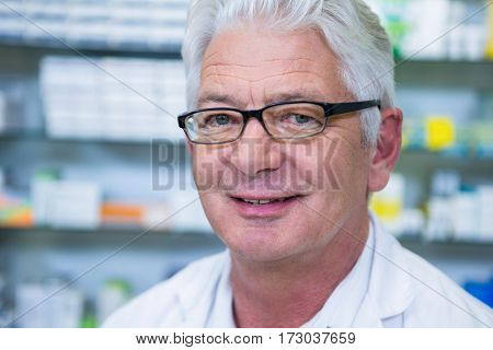 Portrait of smiling pharmacist in spectacles at pharmacy