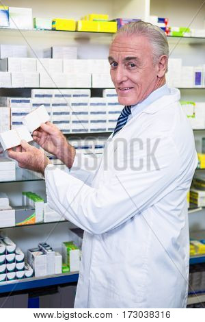 Portrait of pharmacist checking boxes of medicine in pharmacy