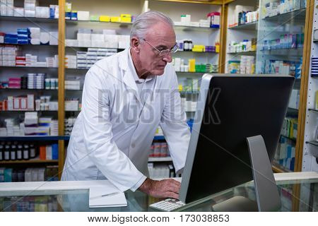 Pharmacist using computer at pharmacy