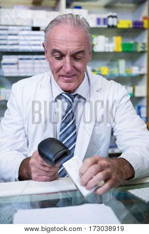 Pharmacist using barcode scanner on medicine box in pharmacy