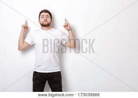 handsome man with beard pointing up. young man in t-shirt looking at camera and pointing away against white wall