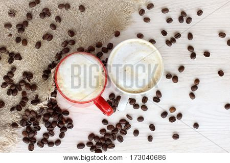 white and red mug with a frothy cappuccino in the background spilling beans top view / aromatic coffee break