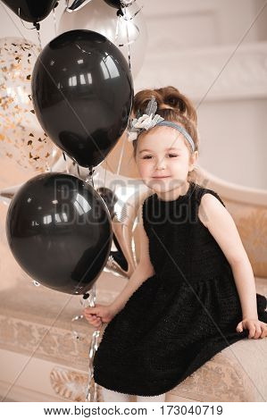 Smiling baby girl 5-6 year old wearing stylish black dress holding balloons sitting on sofa in room. Looking at camera. Celebrating birthday. Childhood.