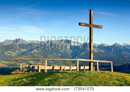 Wooden summit cross with sublime view to a mountain range. Ofterschwanger Horn, Bavaria, Germany.
