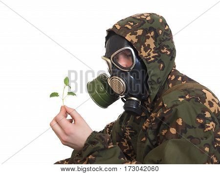 Soldier in a gas mask with a young green plant in hands. White background