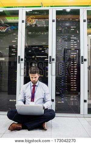Technician using laptop in server room