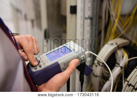 Mid section of technician using digital cable analyzer in server room