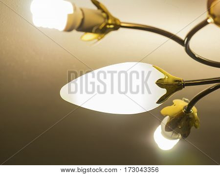 A gold glowing chandelier near the ceiling