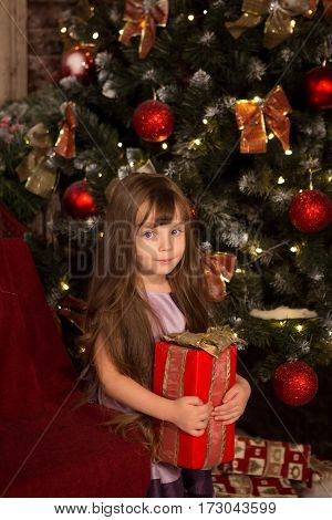 Little girl with christmass gift in her hands