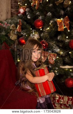 Little girl near a Christmas tree with a gift in their hands waiting for celebration New year