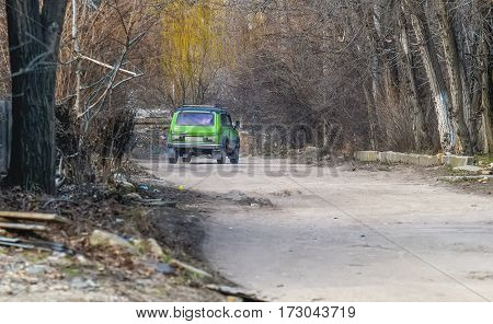 An old road with pits and green car