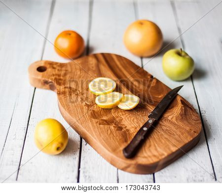 cut lemon and other fruits on a beautiful wooden board on white table
