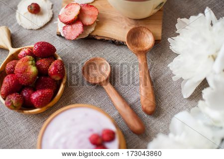 two handcarved small wooden spoons and a healthy breakfast with strawberries