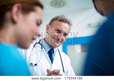 Portrait of smiling doctor standing with surgeons in corridor at hospital