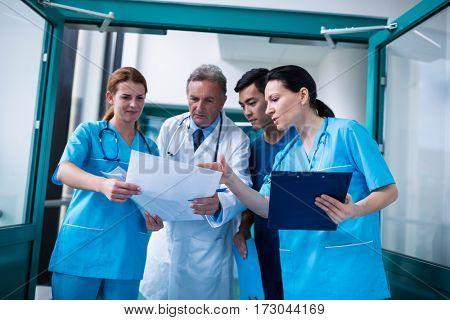 Doctor and surgeons discussing with report in surgical room at hospital