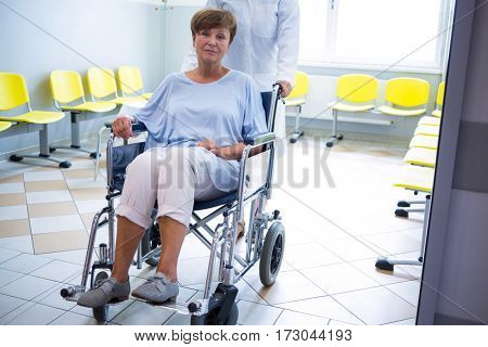 Doctor pushing senior patient on wheelchair in hospital