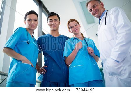 Portrait of doctor and surgeons standing together in corridor at hospital