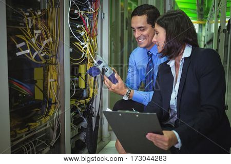 Technicians using digital cable analyzer while analyzing server in server room