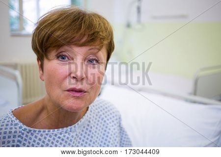 Portrait of smiling patient sitting on bed in hospital