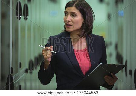 Technician preparing check list in server room