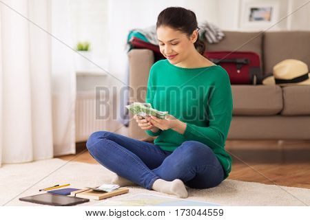 tourism, travel, finances and people concept - happy young woman with money, tablet pc computer and map at home