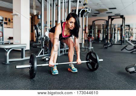 Beautiful Fitness Brunette Woman Lifting Barbell.