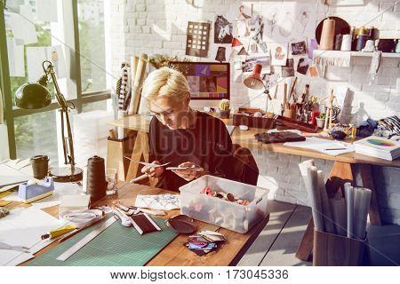 Fashion designer tattooed girl choosing material