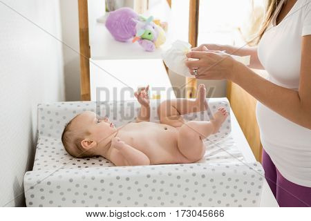 Mother changing the diaper of her baby at home