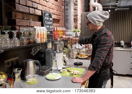 small business, people and service concept - happy man or barman with blender cooking smoothie at vegan cafe