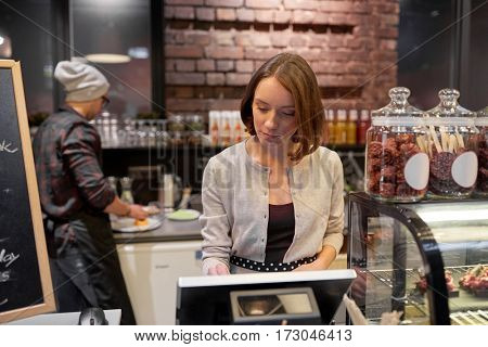 small business, people and service concept - woman or barmaid at counter with cashbox working in cafe or coffee shop
