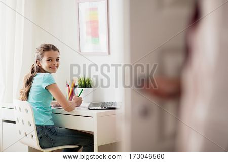 people, children, education and learning concept - happy doing homework at home and mother opens door in her room